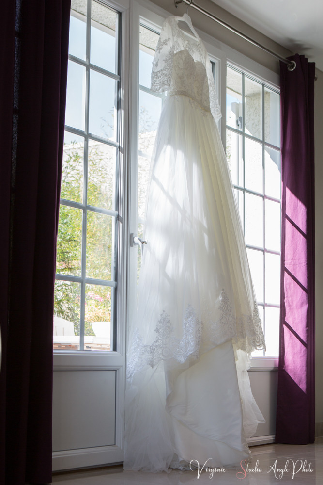 la robe de la mariée suspendue à la fenêtre