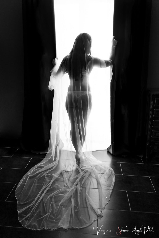 mariée portant son voile devant la fenêtre