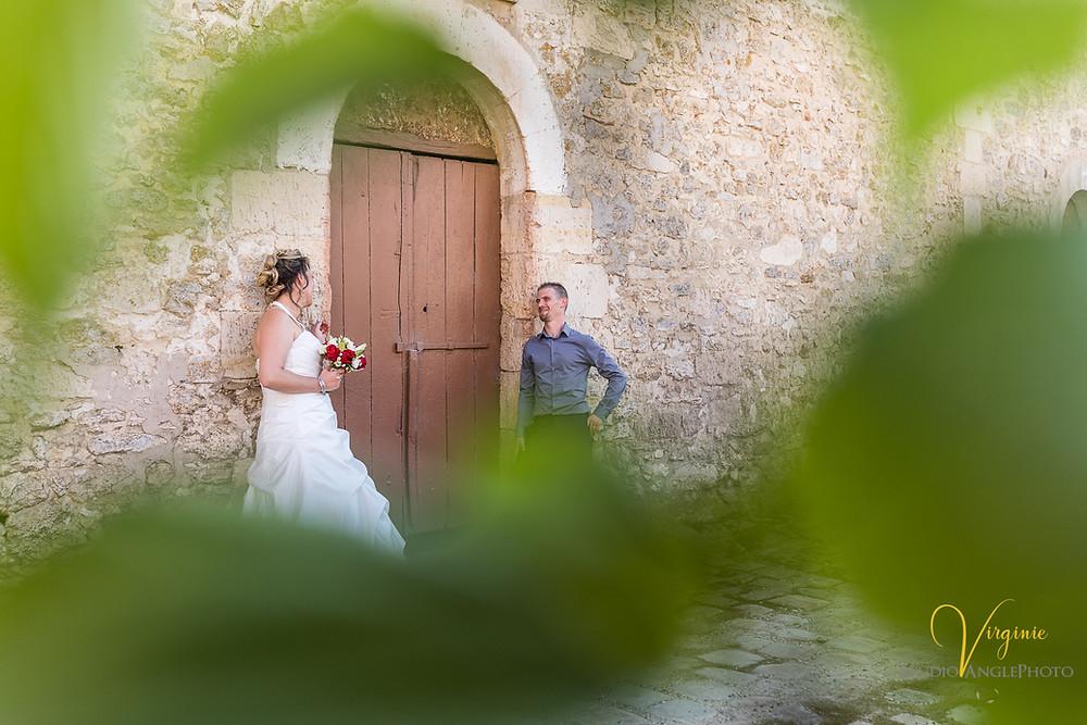 les mariés se regardent amoureusement devant une jolie porte ancienne