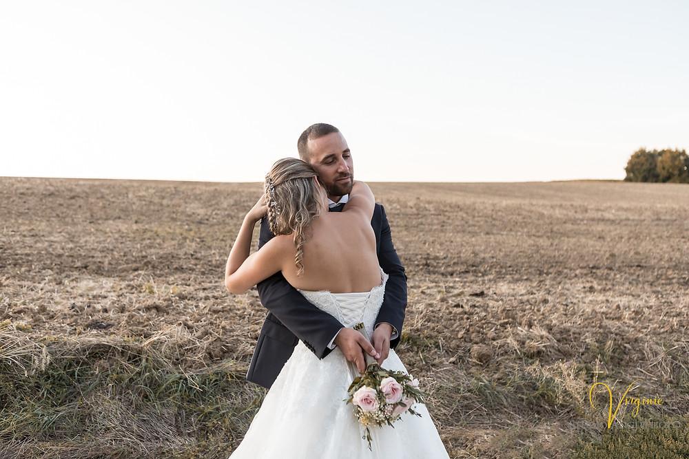 les mariés s'enlacent et le marié tient le bouquet
