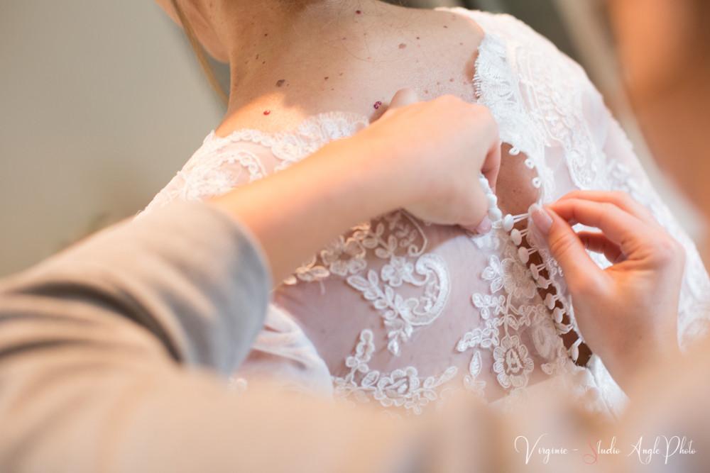 l'amie de la mariée met les boutons de la robe