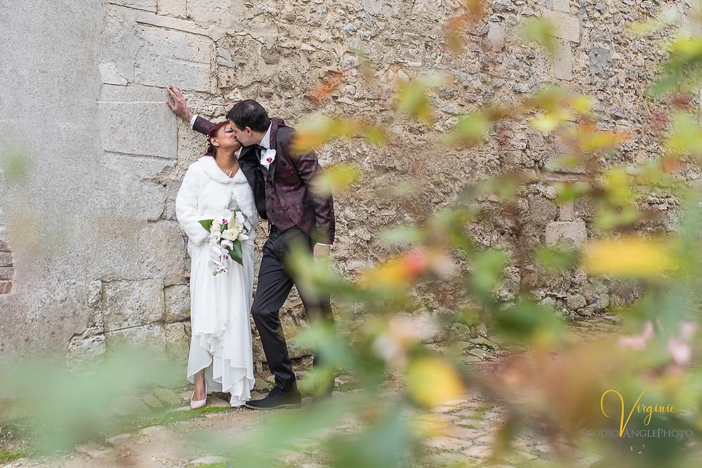 les mariés s'embrassent dans l'allée fleurie