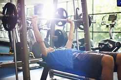 man with weights bench press