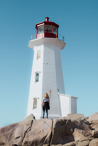 Backpacker Exploring the Base of Peggy's Cove Lighthouse near Halifax, Nova Scotia