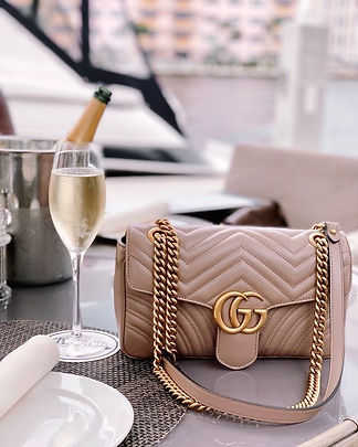 Beautiful, small blush Gucci purse, accompanied by a cold glass of white wine, in a luxurious setting