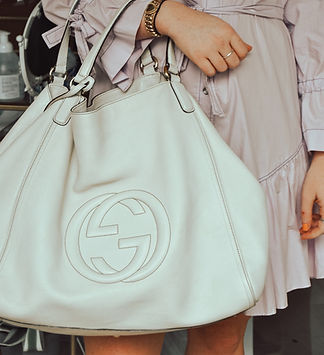 Fashionable woman with beautiful jewelery, holding a large Gucci off-white purse