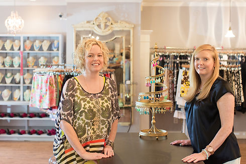 Founders of JT Posh, Jen and Tracy, standing proudly and smiling in their boutique consignment store