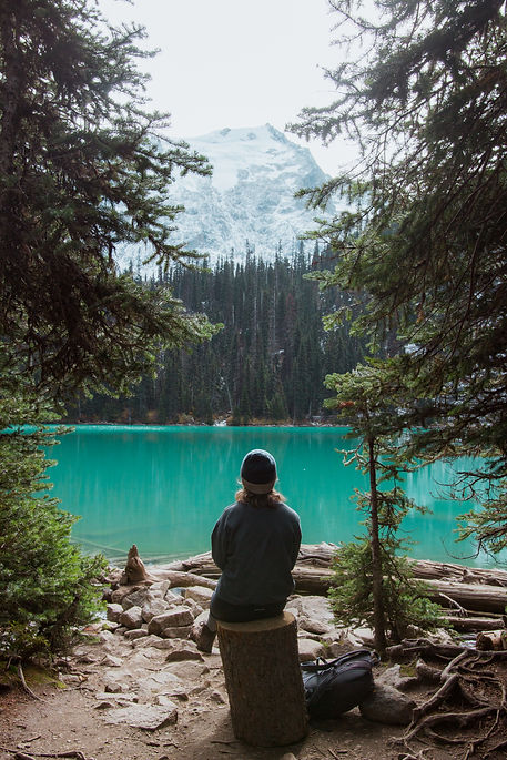 Founder of FML Adventures, Lisa Kurolap looking over the turquoise waters of Joffre Lake in British Columbia. Surrounded by beautiful forests, mountains and lakes.