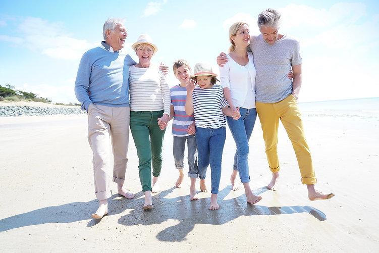 Happy intergenerational family walking on the beach.jpg