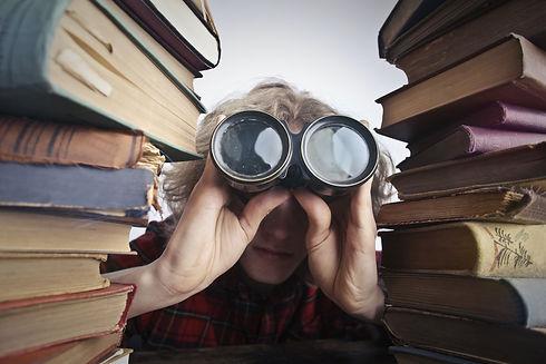 Woman looking through binoculars between two stacks of books.