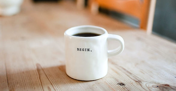 """Coffee cup on table with the word """"begin"""" written on the cup."""