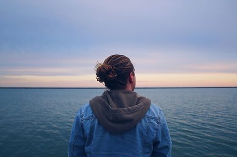 Man looking out at the ocean's horizon.