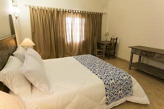 Apartamento de hotel fazenda com cama de casal abajour cortinas luminaria colonial enxoval branco