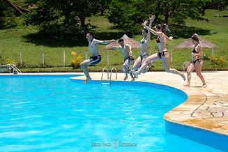 Piscina de Hotel Fazenda com pessoas mergulhando quiosques ao ar livre