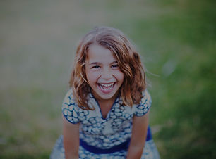Menina sorrindo brincando no gramado hotel fazenda