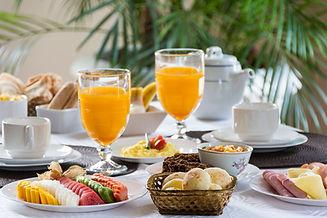 Café da manha de hotel fazenda suco de laranja paes biscoitos geleias mel queijos produtos regioanais