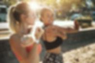 Two fit young women in sportswear smilin