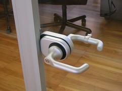 Dettaglio maniglia in metallo per porte in vetro.