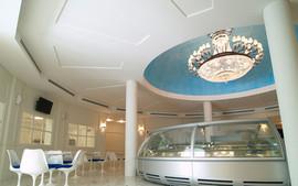 """Area Bar Gelateria: soffitto con gole luminose in gesso e metallo con gap per aria condizionata e led. Rosone in gesso verniciato """"simil cielo"""" e cupola con lampadario."""