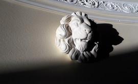 """Particolare in gesso di leone modello """"Venezia"""" per cosciale in metallo rivestito con laminato e cornici decorative."""