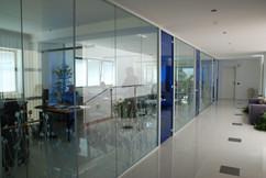 Parete in vetro divisioria per Uffici e Corridoio: parete in vetro colorato a tutt'altezza con profili in alluminio e porte scorrevoli.