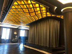 Area Salotto Relax: soffitto curvilineo in metallo verniciato oro e gole luminose con led.