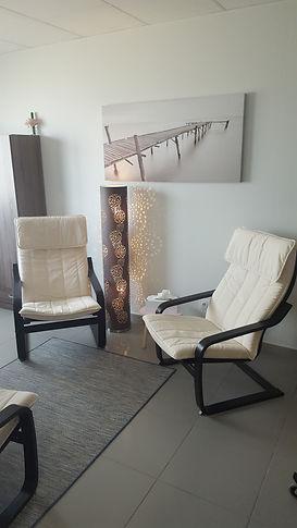 Intérieur du cabinet montrant deux fauteuils confortables ainsi qu'une lampe ajourée