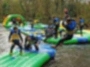 Family's having fun getting wet on inflatable obstacles at Dorset Water Park