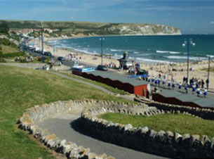 View looking down at Swanage beach, towards headland