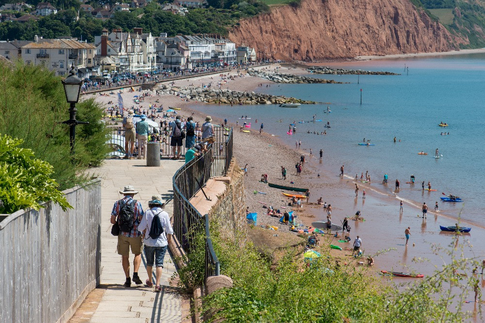 View of Sidmouth town and seafront in East Devon (UK) from the clifftop walkway in Connaught Gardens. Picture taken in summertime when visitors flock to the town. Many people gather at the end of the walkway to look over the railings at the packed beach and sea.