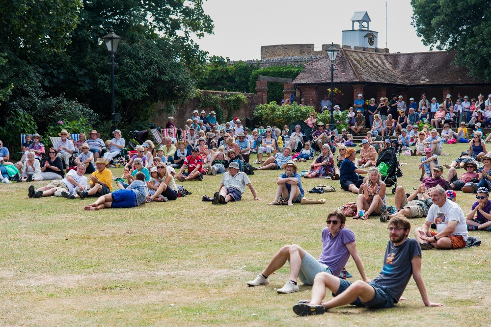 Crowds of people sitting down on the grass lawn to watch the performances taking place in the bandstand during the Sidmouth Folk Festival.