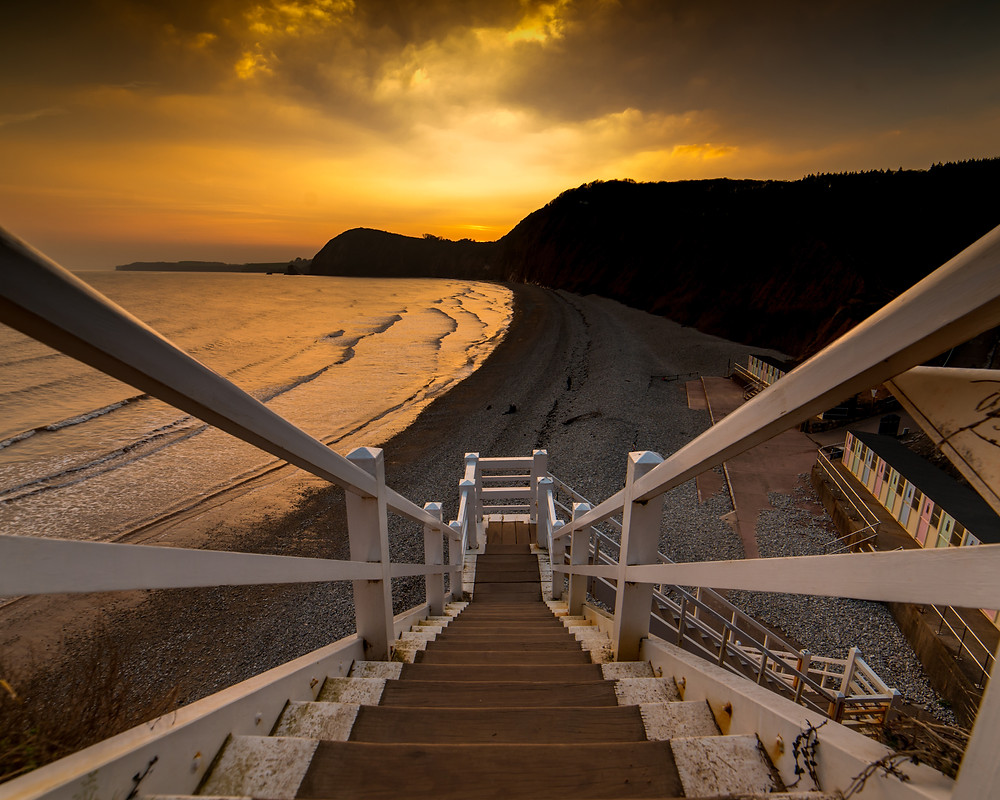 Sunset at Jacob's Ladder beach, Sidmouth. Taken from the top of the ladder looking down with a golden sunset bathing the sea in a warm hue.