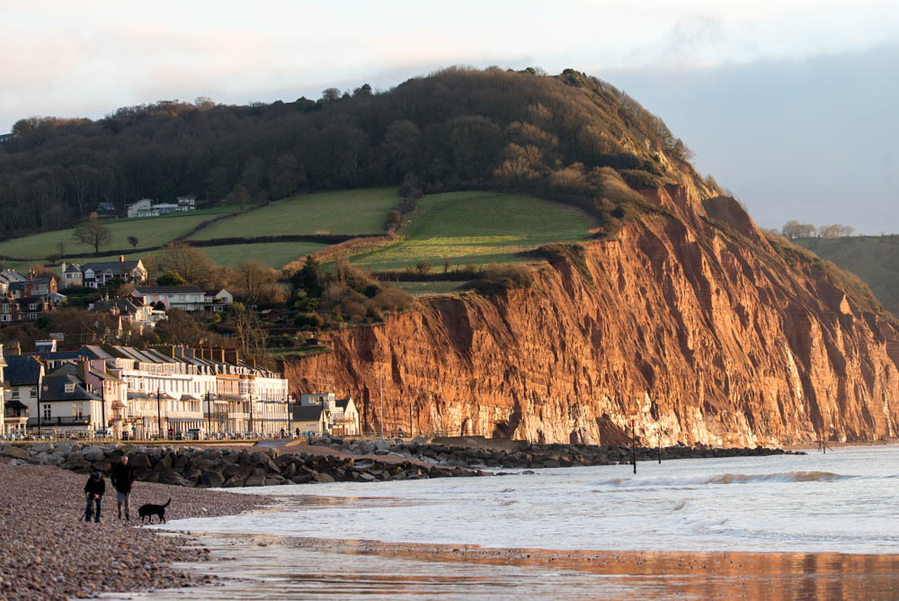 The red cliffs of Salcombe Hill are synonymous with Sidmouth's seafront. This picture shows the iconic red cliffs rising up at the East end of the seafront with the hotels and lifeboat station at the foot of the South West Coast Path.