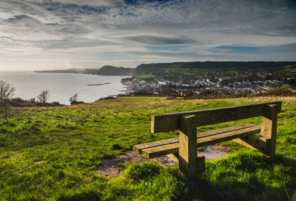 Pictured is the wooden bench that overlooks Sidmouth, High Peak Hill and the coastline at Ladram Bay from the top of Salcombe Hill.