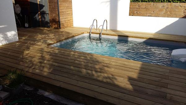 Vue d'ensemble terrasse aménagée autour d'une piscine.