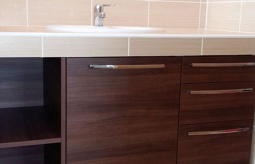 Intégration d'un meuble de salle de bain sur mesure, sous plan de travail maçonné et carrelé.