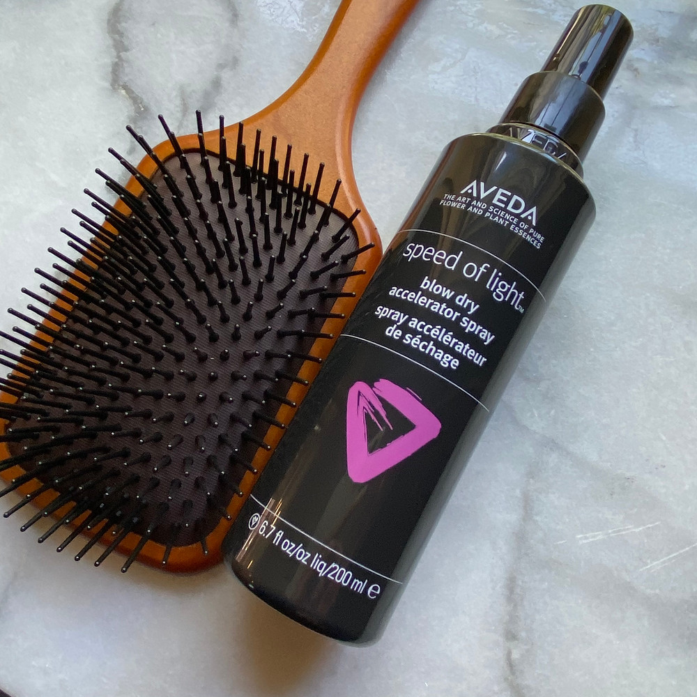Aveda's Speed of Light Blow Dry Accelerator Spray with woodne paddle brush on a marble countertop