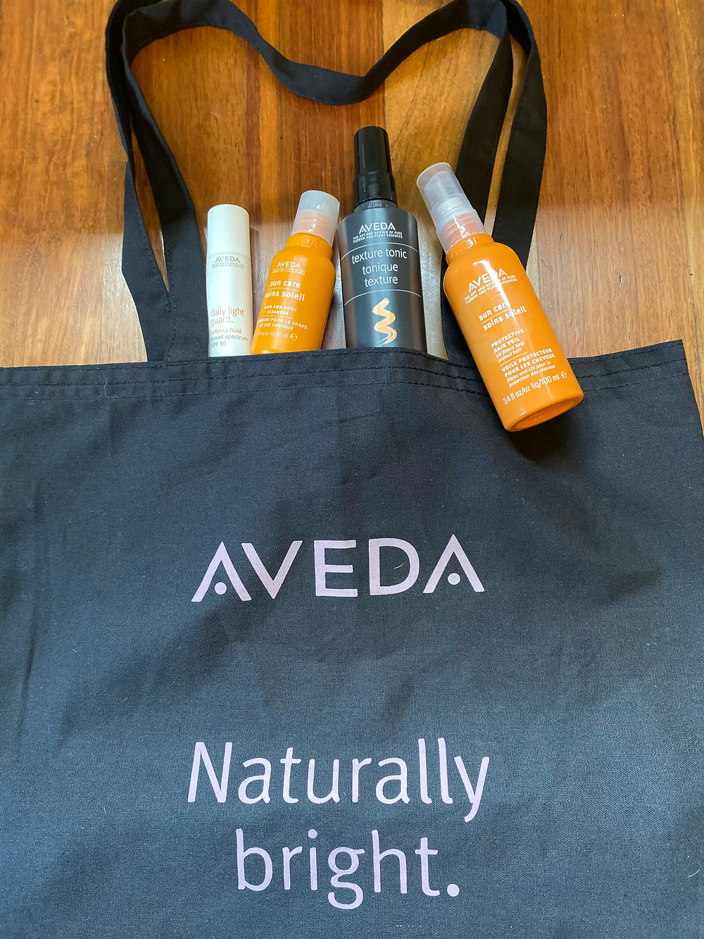 Aveda Naturally Bright tote bag with Aveda products Daily Light Guard, Sun Care Hair Veil, Texture Tonic, and travel size of Sun Care Hair and Body Wash