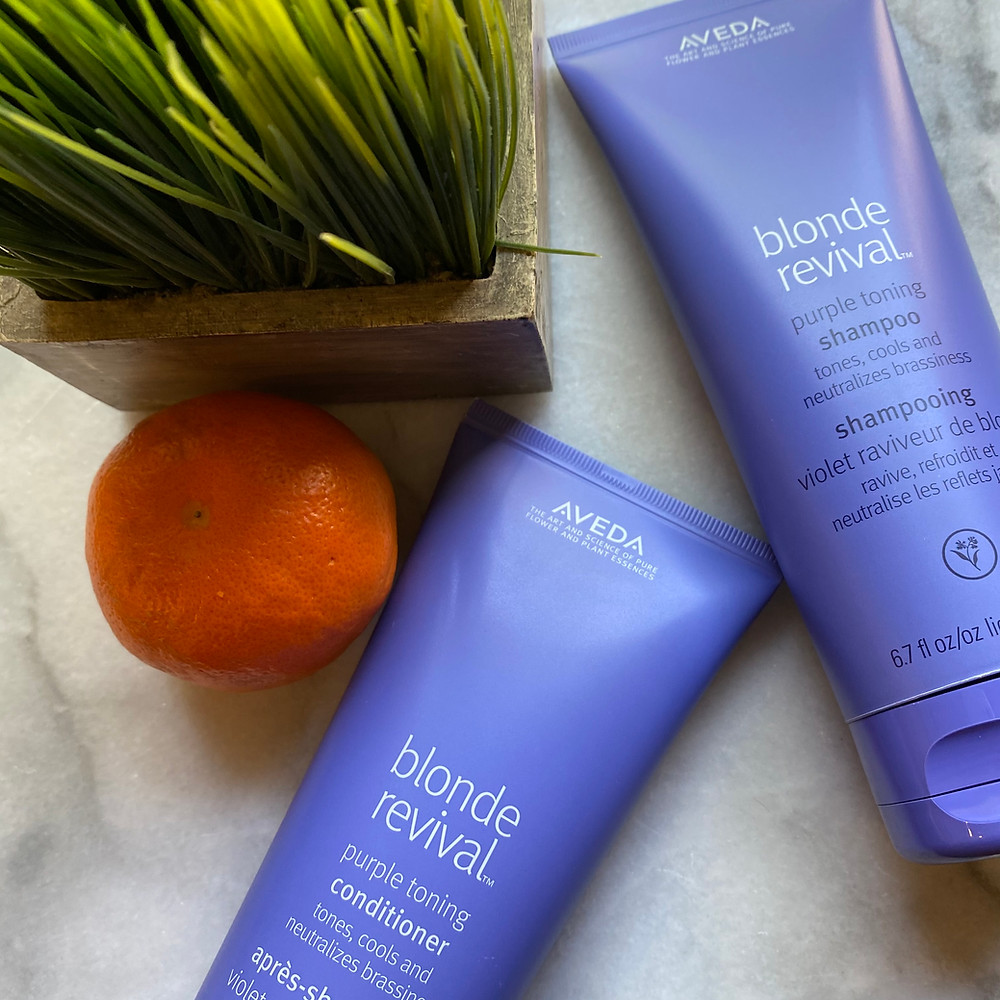 Blonde Revival Purple Toning Shampoo and Conditioner on a marble background with wheat grass and an orange