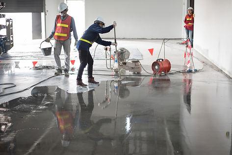Construction worker painting epoxy floor
