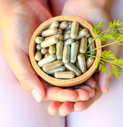 Girl hands holding herbal capsules in wooden bowl.jpg