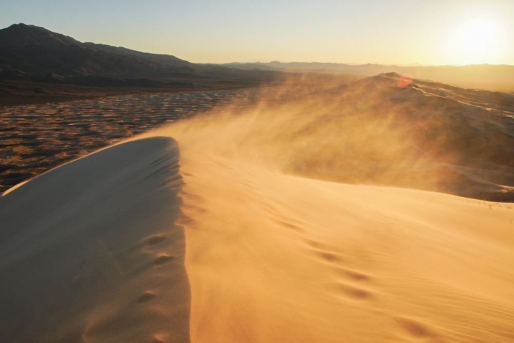 Sand blowing off the top of the Kelso dunes at sunset