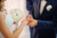 groom puts on a gold wedding ring on the