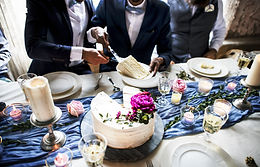 Newlywed gay couple getting cake plate.j