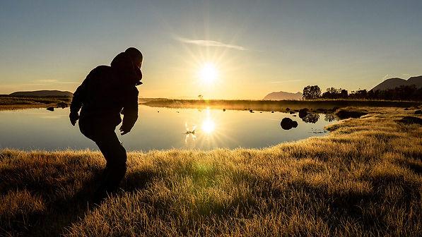 man-throwing-a-stone-into-a-calm-lake-du