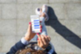 Frau-mit_Smartphone-Screen-auf_Straße-S