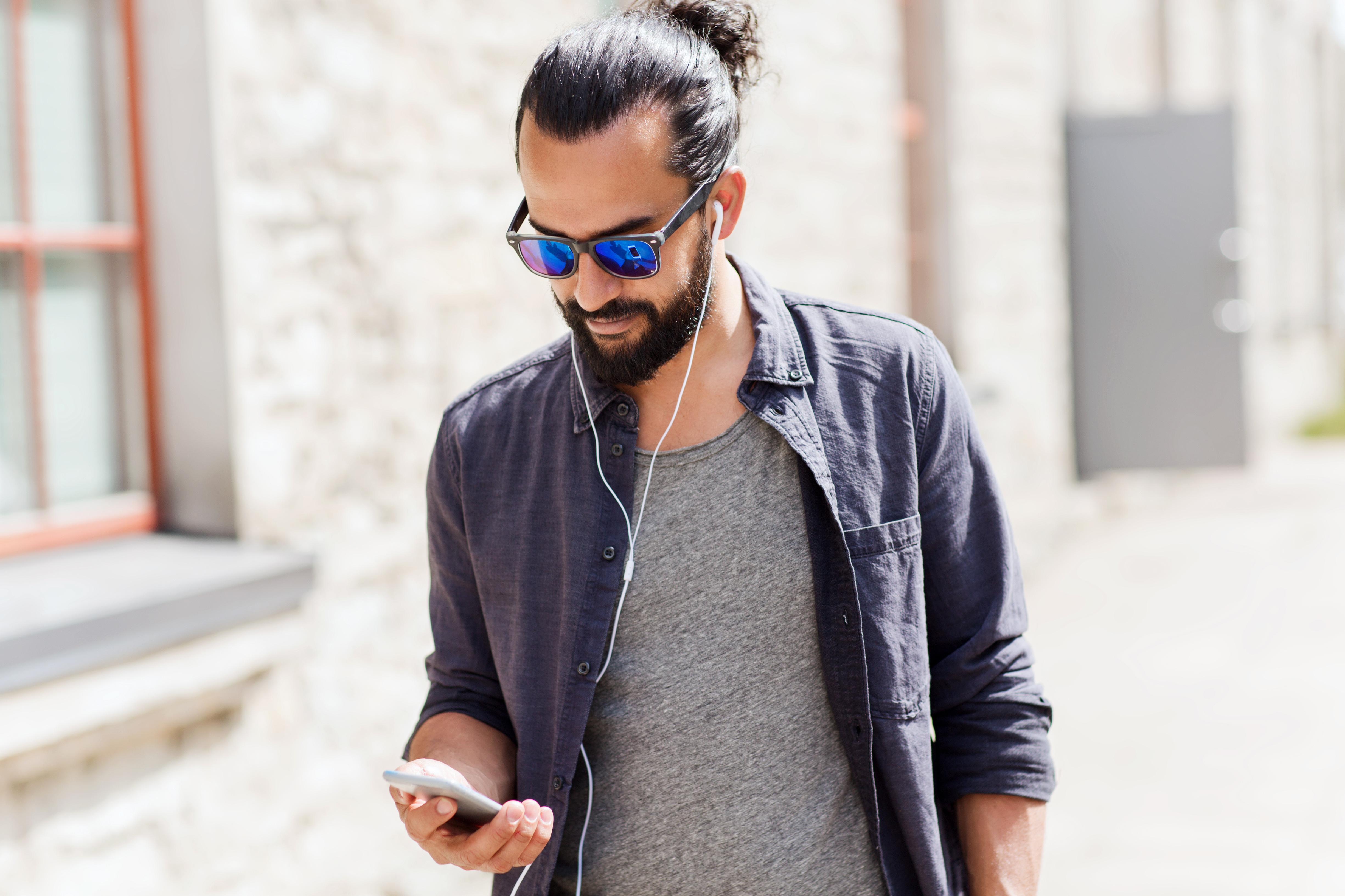 Junger_Mann-Straße-mit_Smartphone-Kopfh
