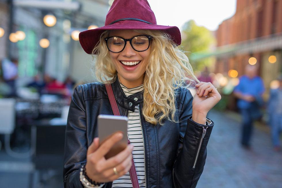 Junge Frau-mit Smartphone-Hut-am Abend-S