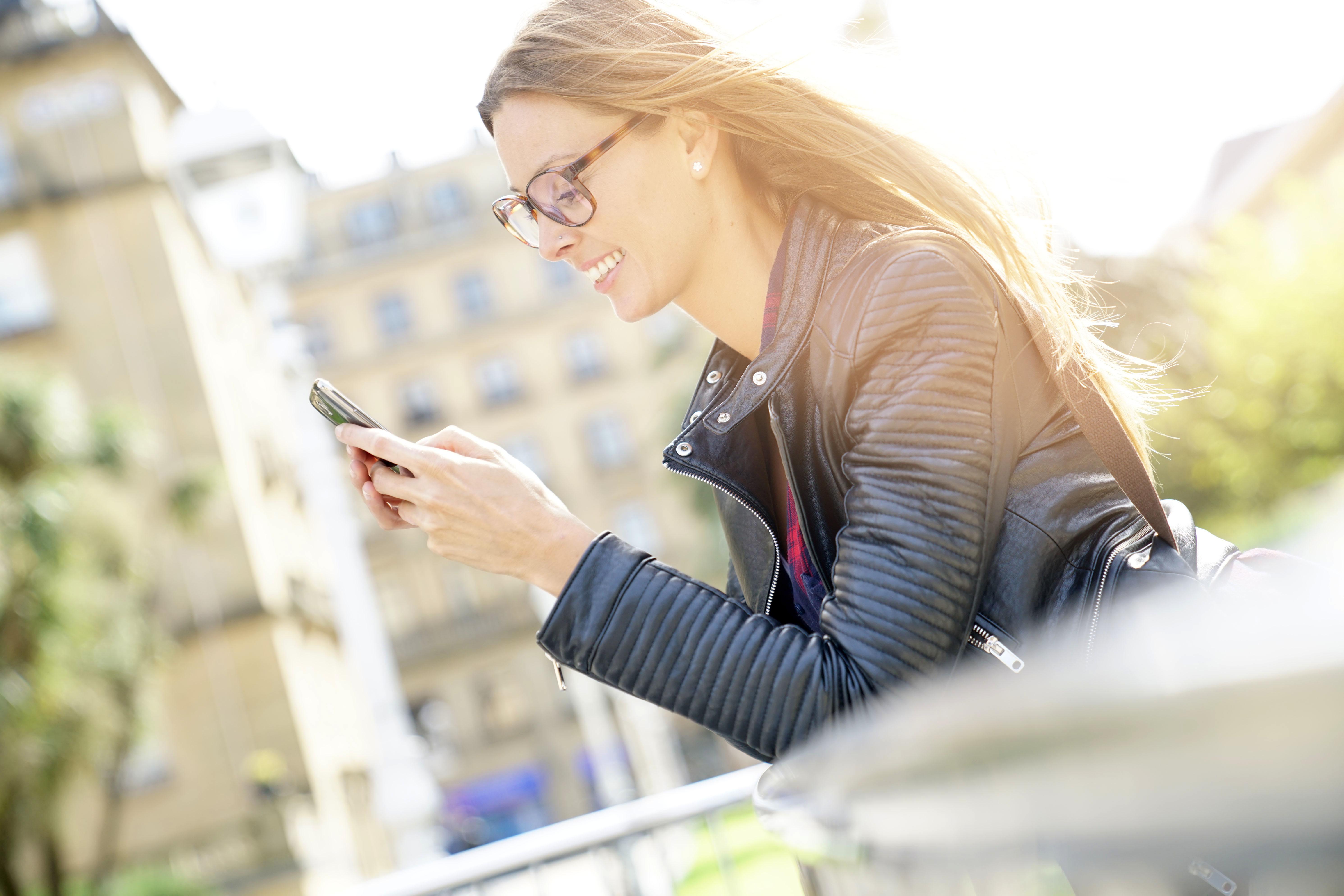 Junge_Frau-mit_Smartphone-Geländer-in_S