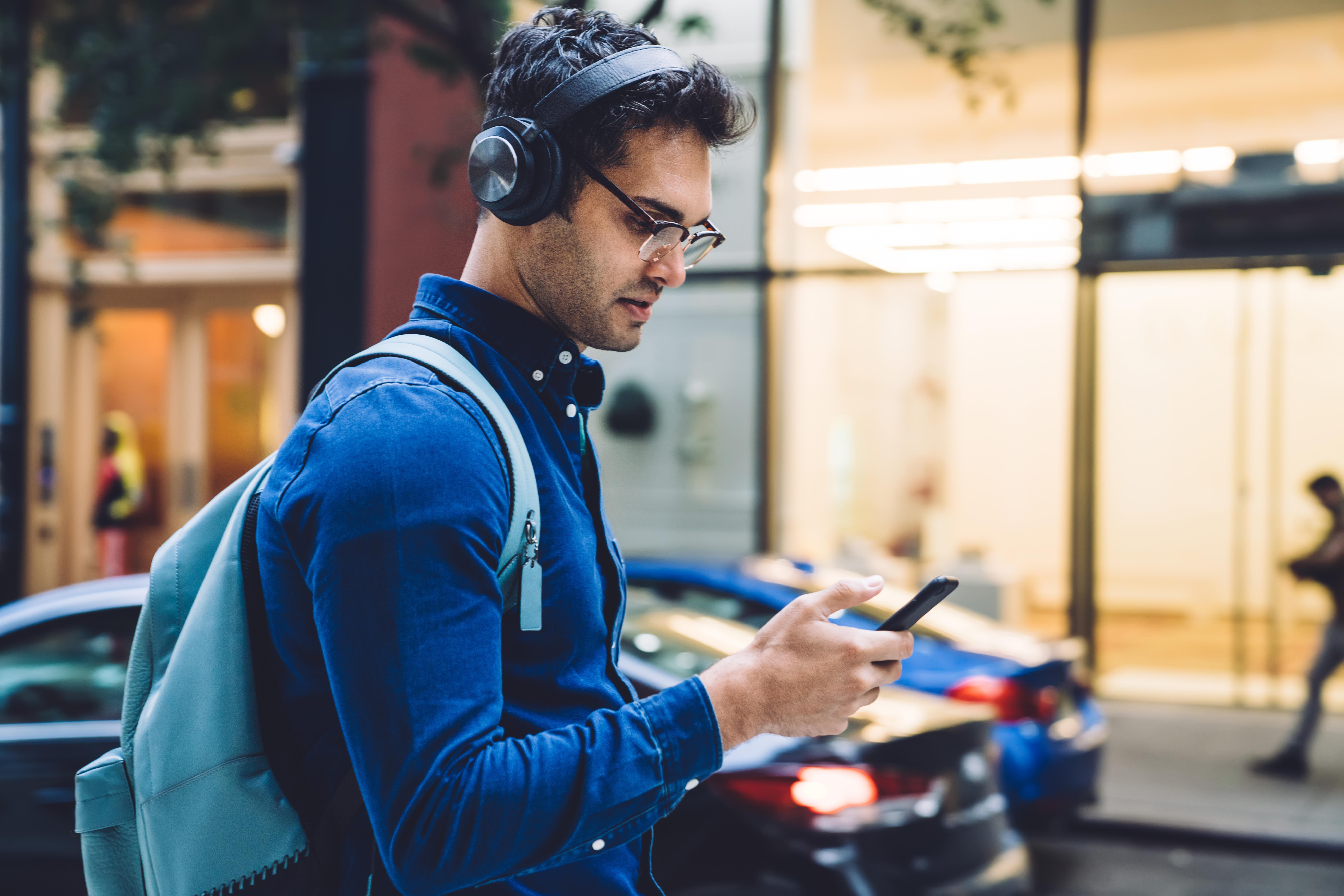 Junger_Mann-mit_Smartphone_&_Kopfhörer-